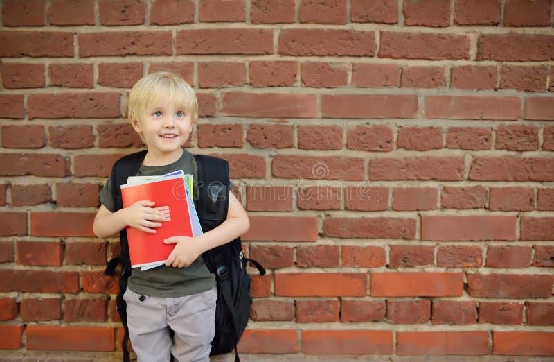 Estudiante con la mochila grande cerca de la construcci?n de escuelas De nuevo a escuela foto de archivo