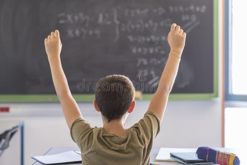 Estudiante con las manos para arriba en sala de clase durante una lección fotos de archivo libres de regalías