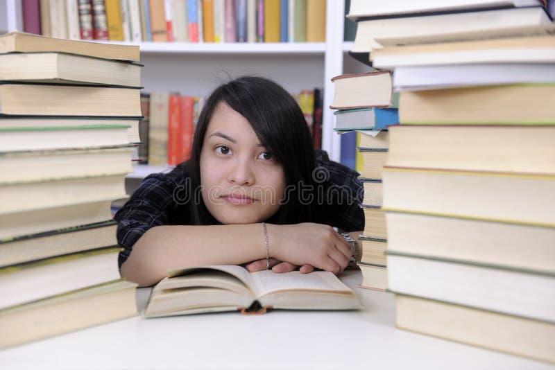 Estudiante con los libros en una biblioteca imágenes de archivo libres de regalías