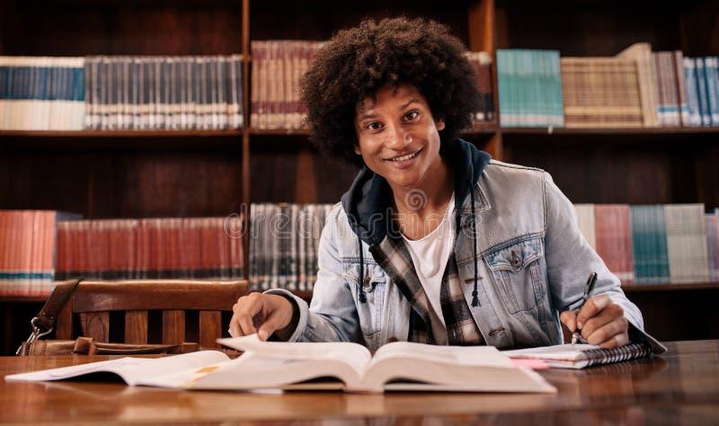 Estudiante confiado joven que estudia en biblioteca foto de archivo libre de regalías