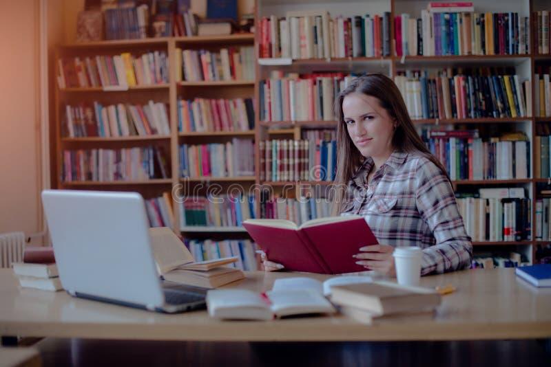 Estudiante confiado que aprende en biblioteca imagen de archivo