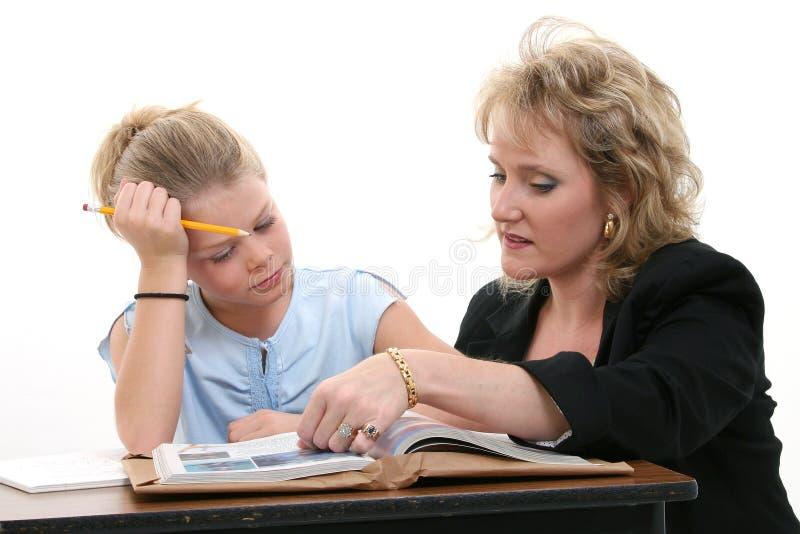 Estudiante de ayuda del profesor en el escritorio imágenes de archivo libres de regalías