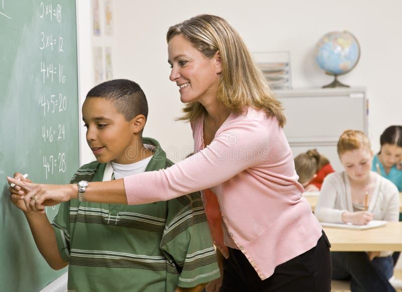 Estudiante de ayuda del profesor en la pizarra foto de archivo
