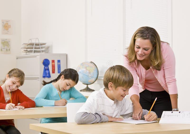 Estudiante de ayuda del profesor en sala de clase imágenes de archivo libres de regalías