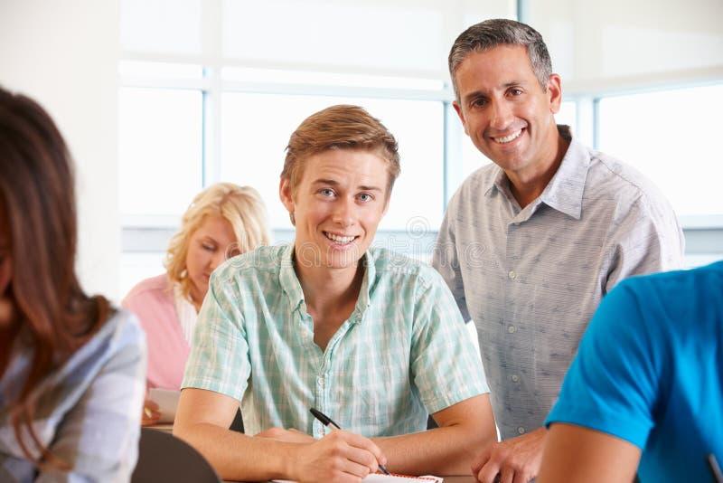 Estudiante de ayuda del profesor particular en clase imágenes de archivo libres de regalías