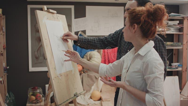 Estudiante de explicación femenino del profesor de arte cómo medir proporciones de la cara foto de archivo libre de regalías