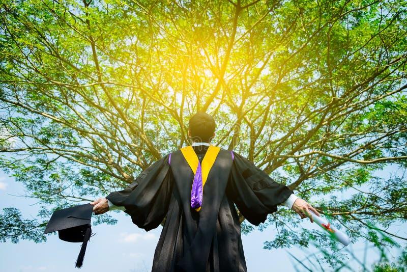 Estudiante de graduación acertado con el fondo de la naturaleza imagen de archivo