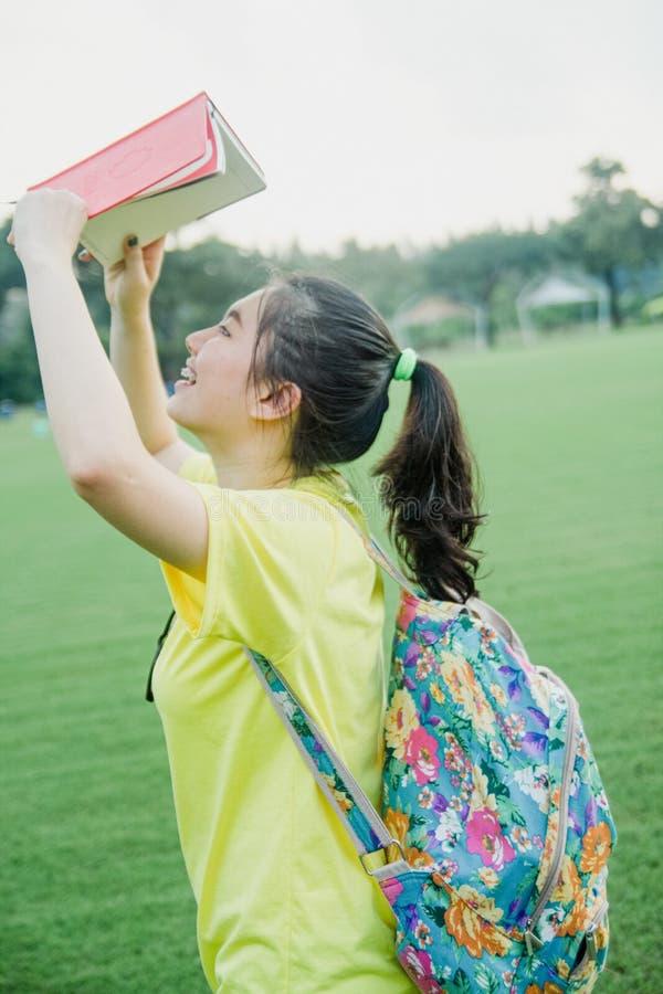 Estudiante de la chica joven que se divierte en campo de hierba en la tarde en campus fotografía de archivo