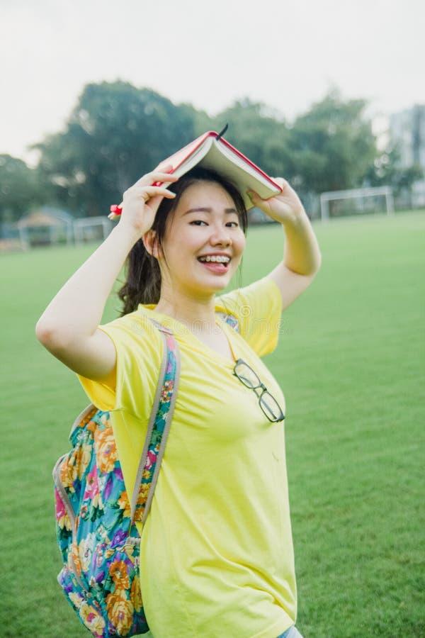 Estudiante de la chica joven que se divierte en campo de hierba en la tarde en campus foto de archivo libre de regalías
