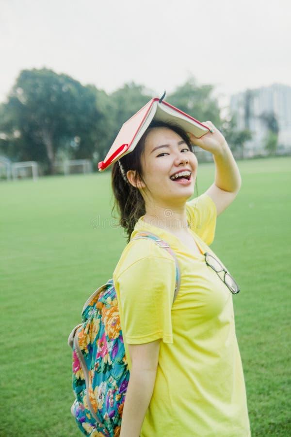 Estudiante de la chica joven que se divierte en campo de hierba en la tarde en campus foto de archivo