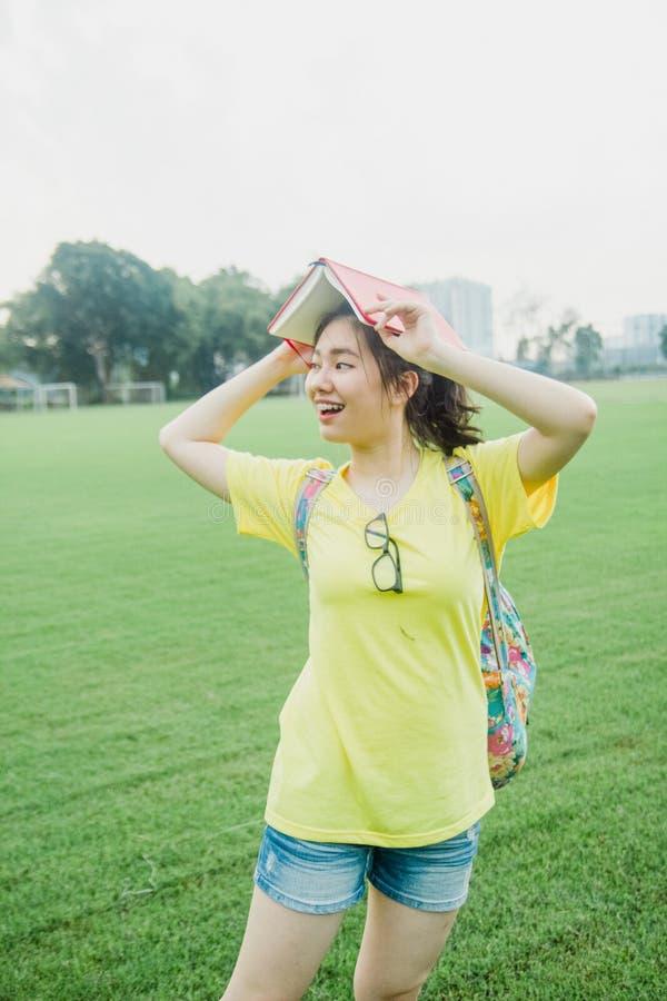 Estudiante de la chica joven que se divierte en campo de hierba en la tarde en campus imagenes de archivo