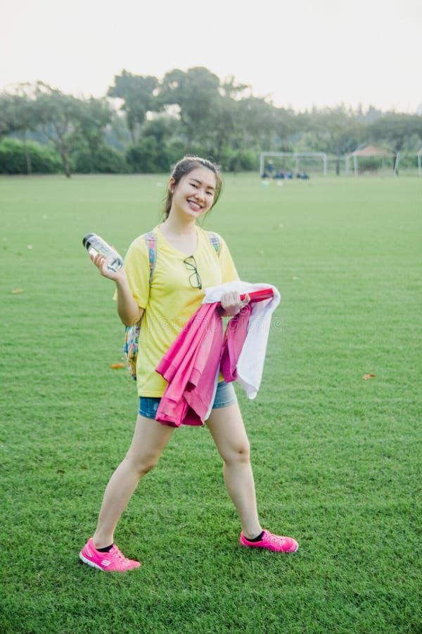Estudiante de la chica joven que se divierte en campo de hierba en la tarde en campus fotos de archivo