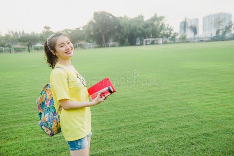 Estudiante de la chica joven que se divierte en campo de hierba en la tarde en campus fotografía de archivo libre de regalías