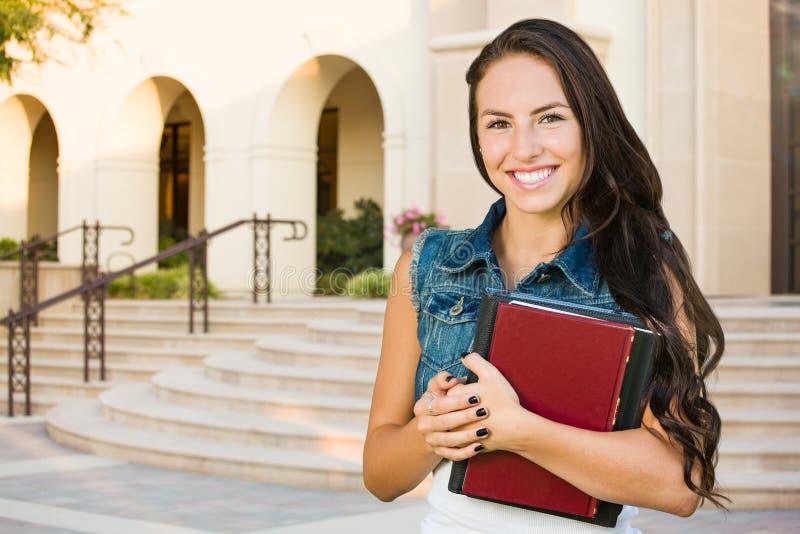 Estudiante de la chica joven de la raza mixta con los libros de escuela en campus imagen de archivo libre de regalías