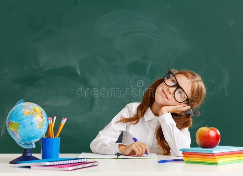 Estudiante de la colegiala del niño sobre la pizarra de la escuela foto de archivo