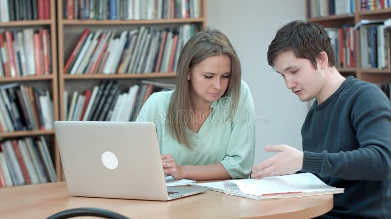 Estudiante de la High School secundaria que trabaja en biblioteca después de clases, usando el ordenador portátil foto de archivo libre de regalías
