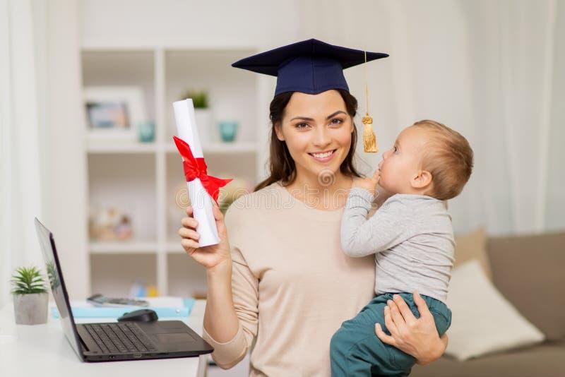 Estudiante de la madre con el bebé y el diploma en casa fotografía de archivo libre de regalías