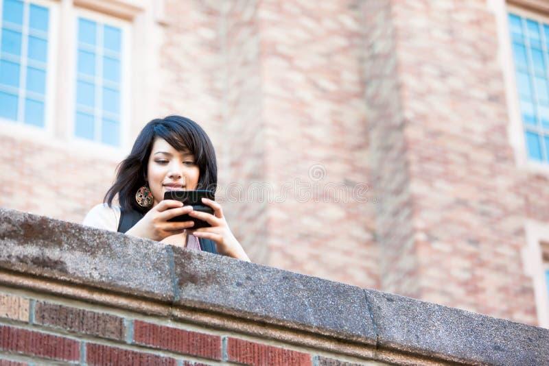 Estudiante de la raza mezclada texting imagen de archivo libre de regalías