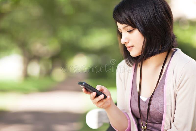 Estudiante de la raza mezclada texting fotografía de archivo libre de regalías