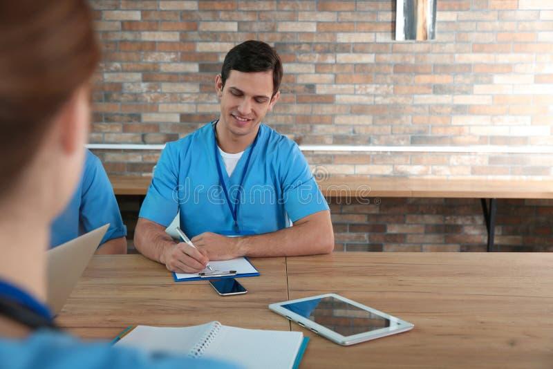 Estudiante de medicina con estudiar de los groupmates foto de archivo