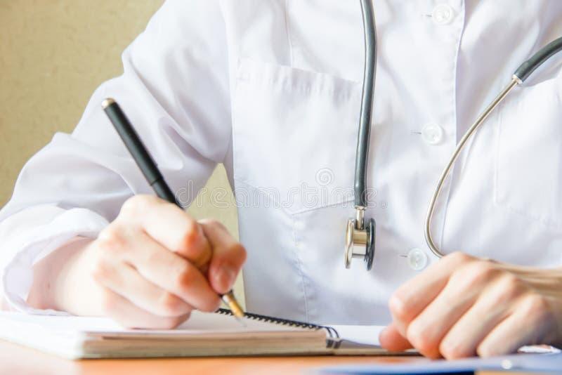 Estudiante de medicina femenino joven que usa smartphone moderno en el hospital, escribiendo en el cuaderno Cierre encima del lan imagen de archivo libre de regalías