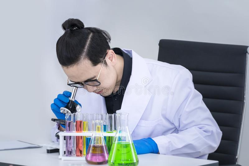 Estudiante de medicina hermoso joven con los microscopios y el tubo de ensayo del color imagen de archivo libre de regalías
