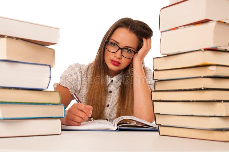 Estudiante de mujer caucásico asiático subrayado que aprende en toneladas de libros imagen de archivo