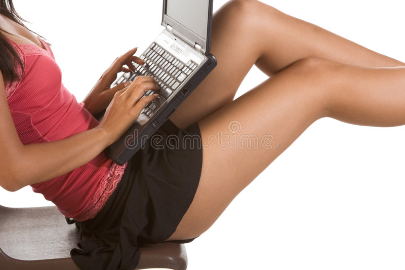 Estudiante de mujer con la computadora portátil en las piernas que pulsa el teclado fotografía de archivo libre de regalías