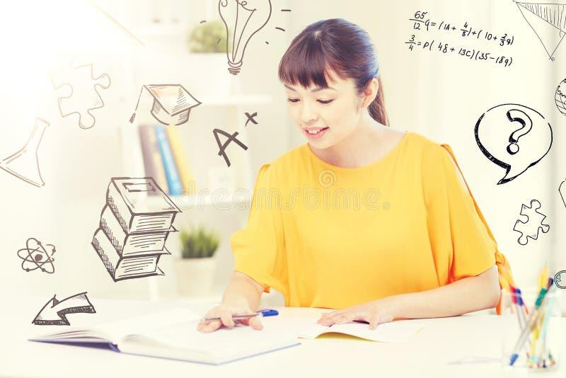 Estudiante de mujer joven asiático feliz que aprende en casa fotografía de archivo libre de regalías