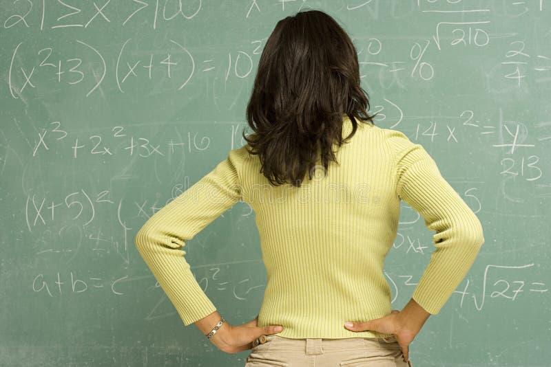 Estudiante de pie delante de la pizarra fotos de archivo