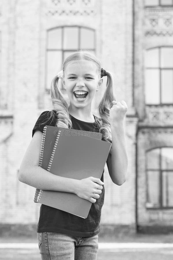 Estudiante de secundaria Un niño pequeño y sonriente cutáneo sostiene los libros de texto de la institución educativa Niña adorab foto de archivo
