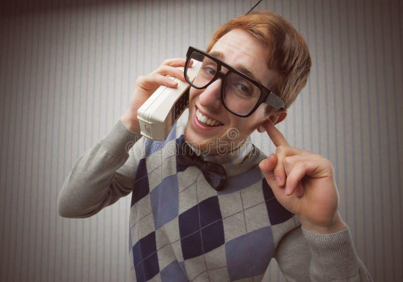 Hombre del empollón con un teléfono móvil viejo fotografía de archivo libre de regalías