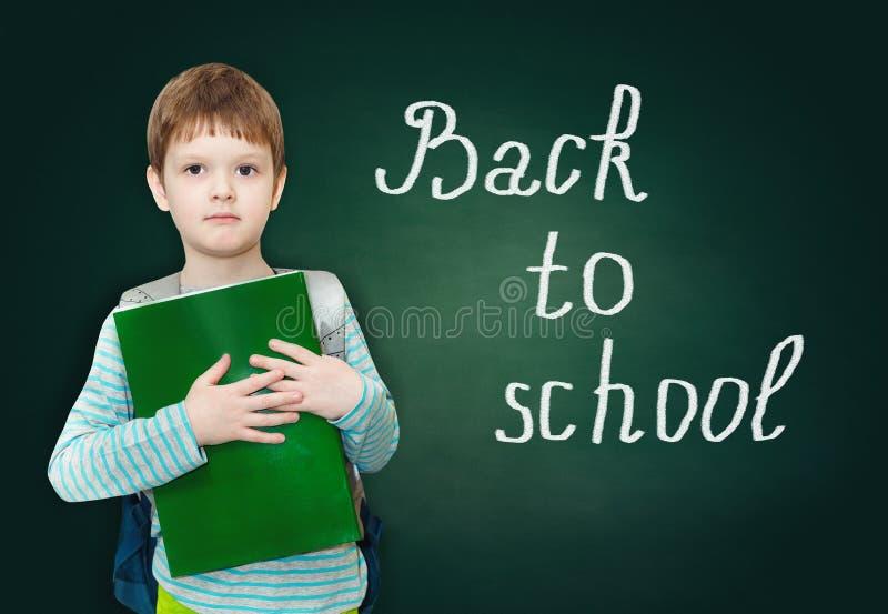 Estudiante del muchacho con el bolso y libros en una pizarra verde con el wo fotos de archivo