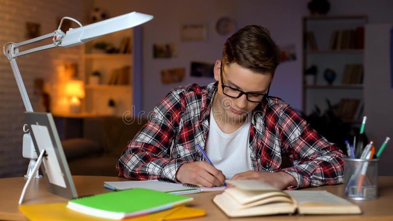 Estudiante diligente que hace su hometask en el campus, trabajando en proyecto del diploma foto de archivo libre de regalías