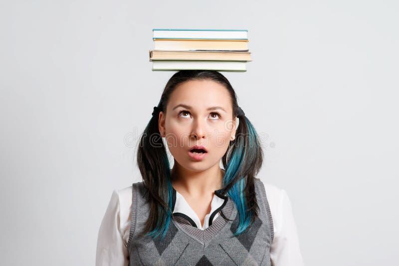 Estudiante divertida con una pila de libros en su cabeza imagenes de archivo