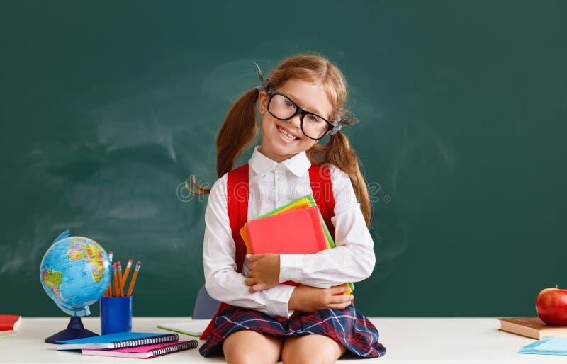 Estudiante divertida de la colegiala del niño sobre la pizarra de la escuela foto de archivo
