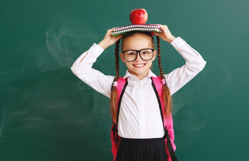 Estudiante divertida de la colegiala del niño sobre la pizarra de la escuela foto de archivo libre de regalías