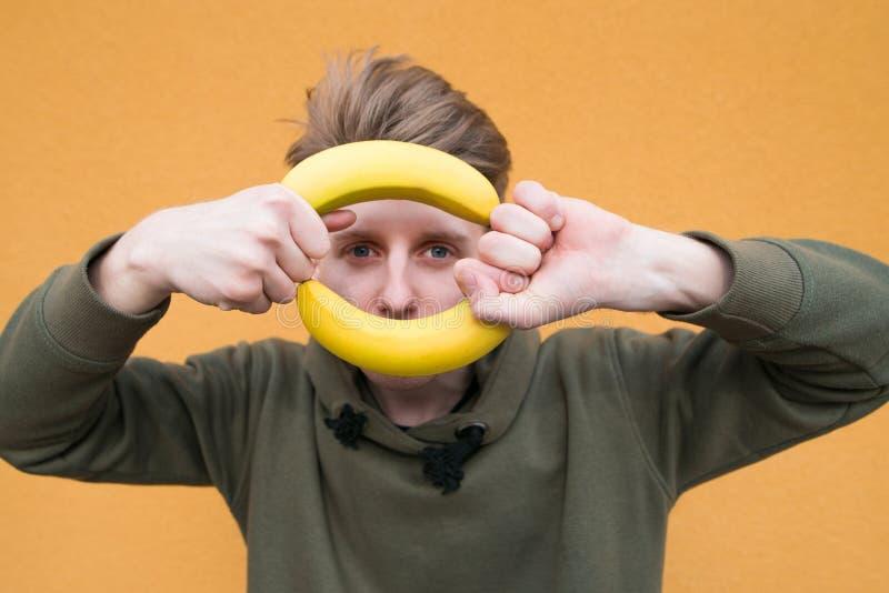 Estudiante divertido con los plátanos en sus manos en el fondo de una pared anaranjada fotos de archivo libres de regalías