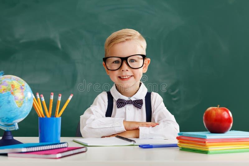 Estudiante divertido del muchacho del colegial del niño sobre la pizarra de la escuela imagenes de archivo