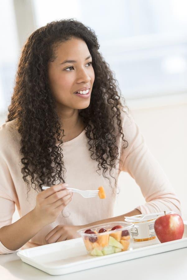 Estudiante Eating Fruit Salad en cantina de universidad foto de archivo