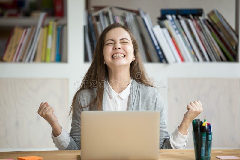 Estudiante emocionado que siente eufórico celebrando el triunfo en línea s imagenes de archivo