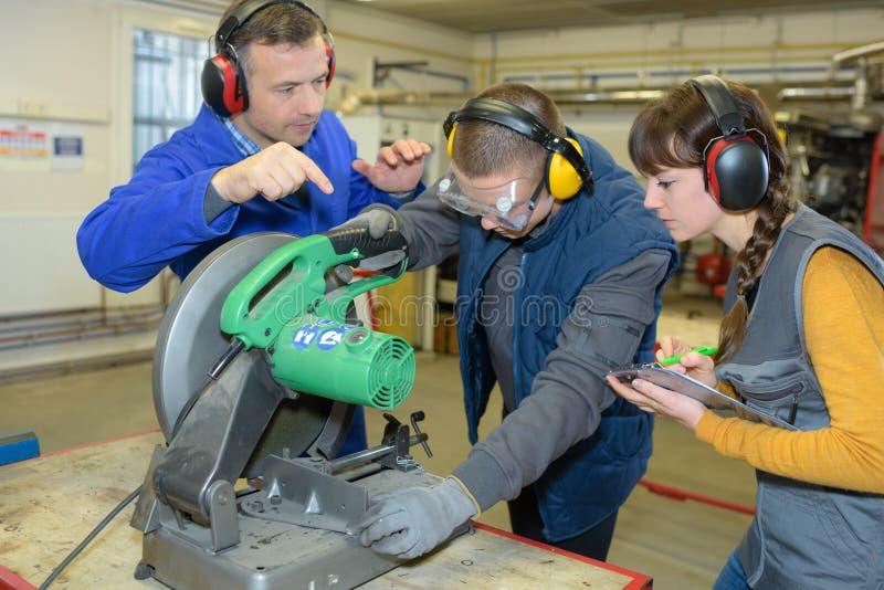 Estudiante en clase de las industrias siderúrgicas usando la sierra circular imagen de archivo