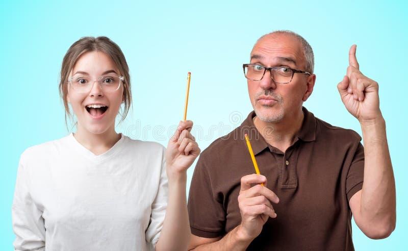 Estudiante en los vidrios y el profesor blanco del camiseta y mayor que señalan una idea que parece muy emocionada fotos de archivo