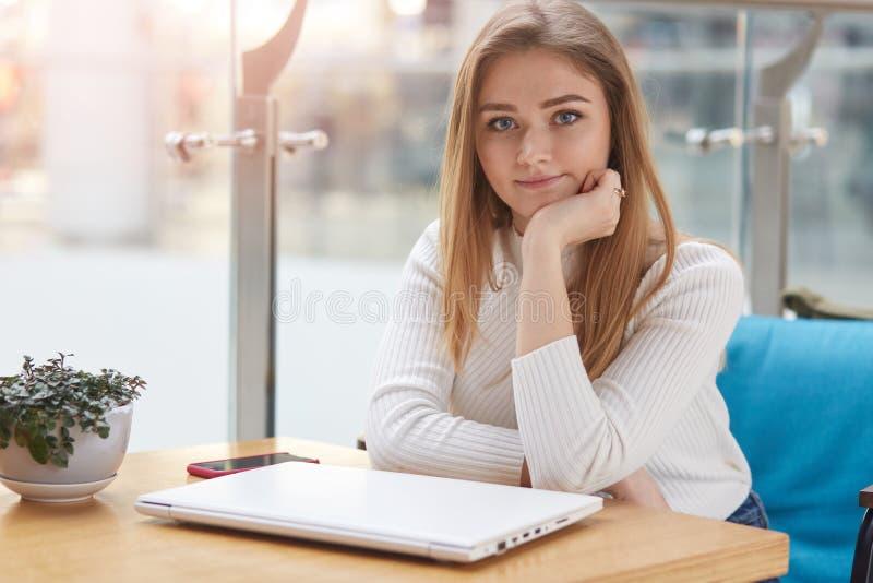 Estudiante encantador que disfruta de la reclinación en café acogedor La chica joven se sienta en la tabla con el ordenador portá foto de archivo