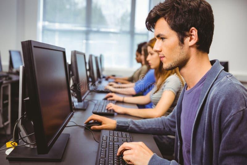 Estudiante enfocado en clase del ordenador foto de archivo