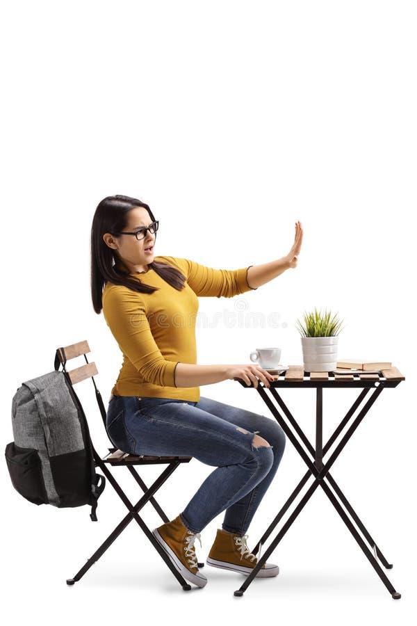 Estudiante enojado en un café que se sienta en una tabla con café y que gesticula la parada con la mano fotografía de archivo