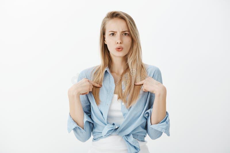 Estudiante europeo preguntado pasmado con el pelo rubio, señalando en sí misma con la expresión desorientada, siendo fotos de archivo