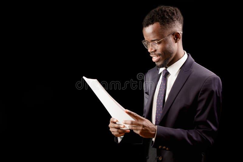 Estudiante feliz africano que lleva el traje elegante que lee un informe foto de archivo