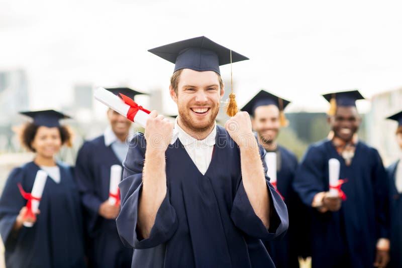 Estudiante feliz con el diploma que celebra la graduación imagen de archivo libre de regalías