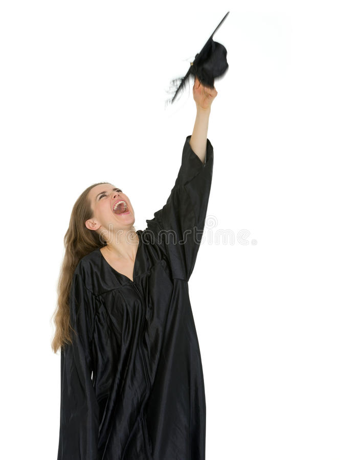 Estudiante feliz de la graduación que lanza para arriba el casquillo imagenes de archivo
